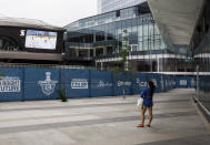 FILE - In this Aug. 24, 2020, file photo, a woman watches a hockey game on the big screen just outside the bubble at the NHL Western Conference Stanley Cup hockey playoffs in Edmonton, Alberta. The NBA had teams in the bubble for three months. The NHL playoff bubble lasted 65 days from the time teams arrived in Toronto and Edmonton, Alberta, until Tampa Bay won the Stanley Cup. Officials from both leagues beamed that mask, distancing and other protocols were still being followed strictly on the final day. (Jason Franson/The Canadian Press via AP, File)