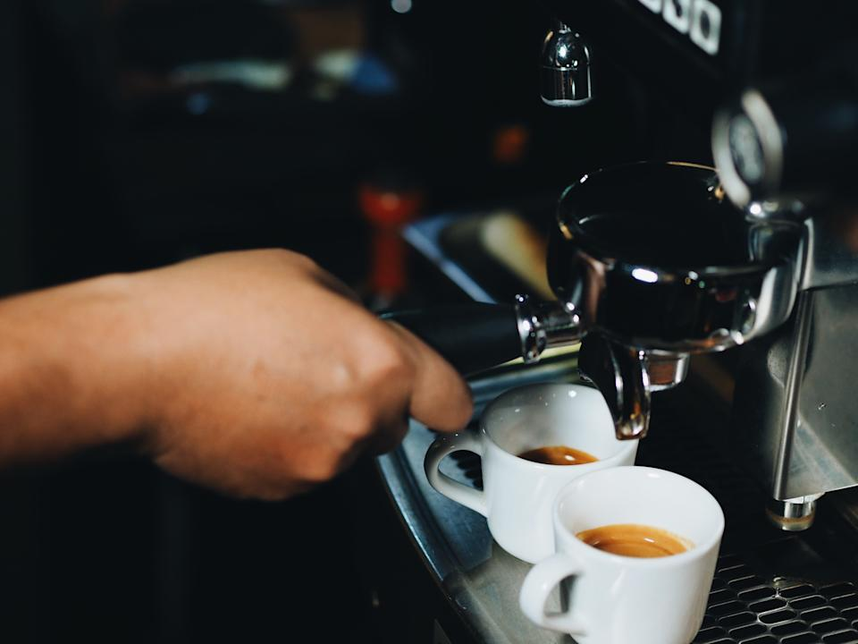 A worker operating a coffee machine.