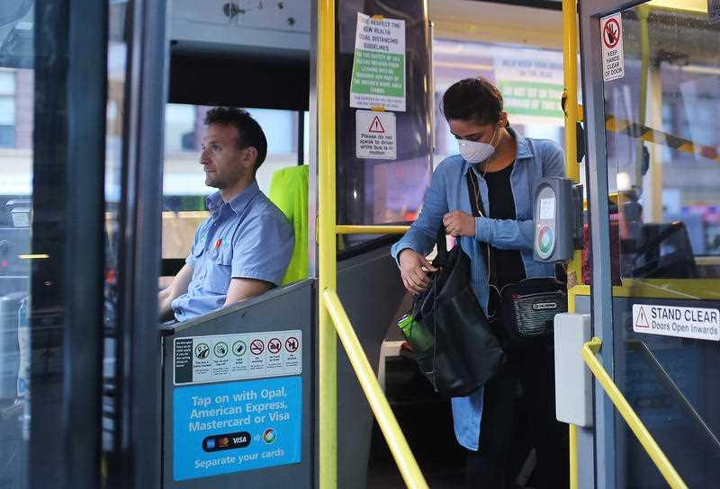 A woman wearing a mask as a preventative measure against the coronavirus disease (COVID-19) boards a public bus at Railway Square bus station in Sydney.