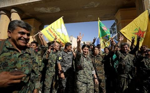 """Fighters of Syrian Democratic Forces gesture the """"V"""" sign in Raqqa, Syria - Credit: Reuters"""