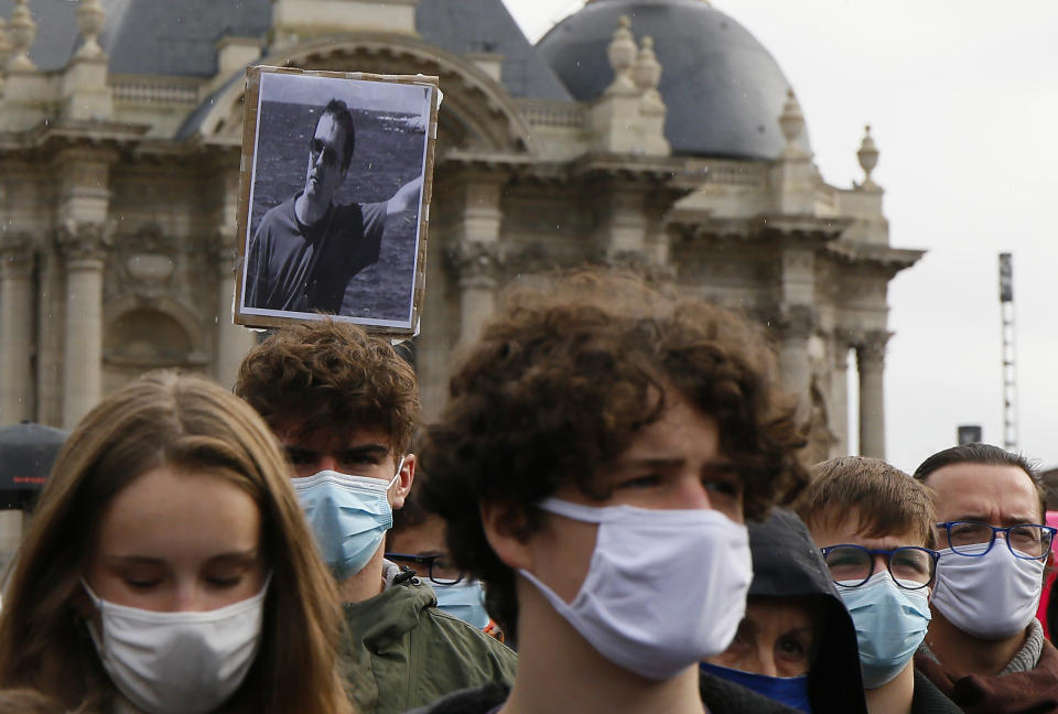 A portrait of Samuel Paty is held up as people gather on Republique square in Lille, northern France, Sunday Oct. 18, 2020. Demonstrators in France on Sunday took part in gatherings in support of freedom of speech and in tribute to a history teacher who was beheaded near Paris after discussing caricatures of Islam's Prophet Muhammad with his class. (AP Photo/Michel Spingler)