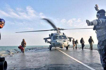 U.S. Navy helicopter from USS America lands on Royal Malaysia Navy's KD Lekiu Frigate 30 during a search and rescue operation for survivors of the USS John S. McCain ship collision in Malaysian waters in this handout photo distributed August 23, 2017. Royal Malaysian Navy Handout via REUTERS