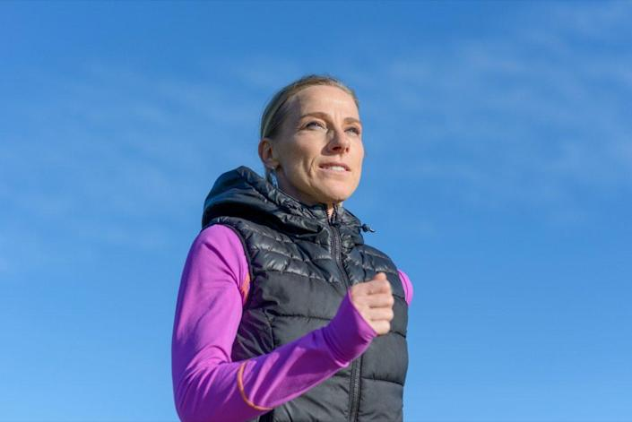 middle-aged woman jogging in winter in a close up low angle view against a sunny blue sky in a healthy active lifestyle