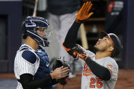 Baltimore Orioles' Anthony Santander looks up as he scores next to New York Yankees catcher Gary Sanchez on a fourth-inning, solo home run off Yankees pitcher Jameson Taillon in a baseball game Wednesday, April 7, 2021, at Yankee Stadium in New York. (AP Photo/Kathy Willens)