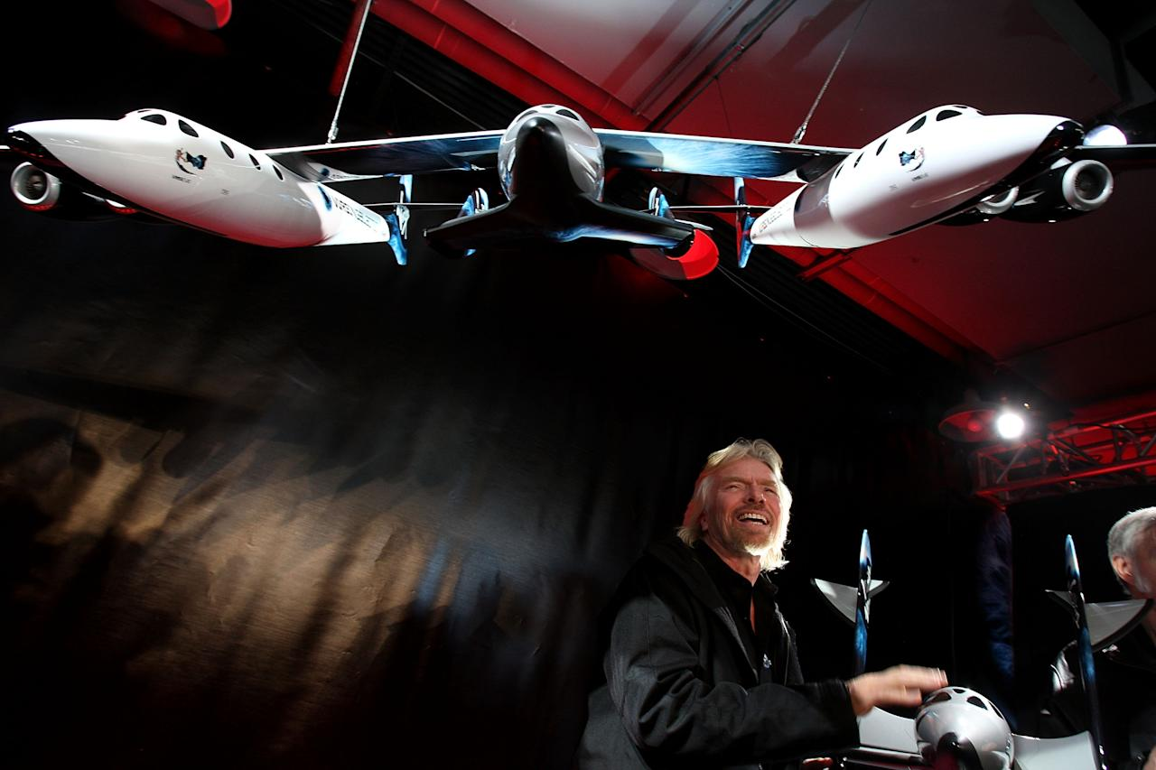 NEW YORK - JANUARY 23:  Sir Richard Branson of Virgin Atlantic stands under a model of a spaceship unveiled at a news conference January 23, 2008 in New York City. Branson hopes the spaceship will be the first to ferry paying passengers into space on a regular schedule. Branson's Virgin Galactic is one of several commercial enterprises currently competing to offer flights to space. Looking to commence the program latter this year, about 200 people have already signed up for the rides, which cost about $200,000 per person.  (Photo by Spencer Platt/Getty Images)