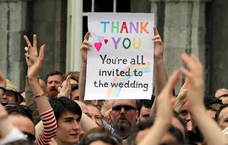 A supporter holds a sign reading 'Thank You - You're All Invited to the Wedding' celebrating the result of the same-sex marriage referendum in Dublin on May 23, 2015 (AFP Photo/Paul Faith)