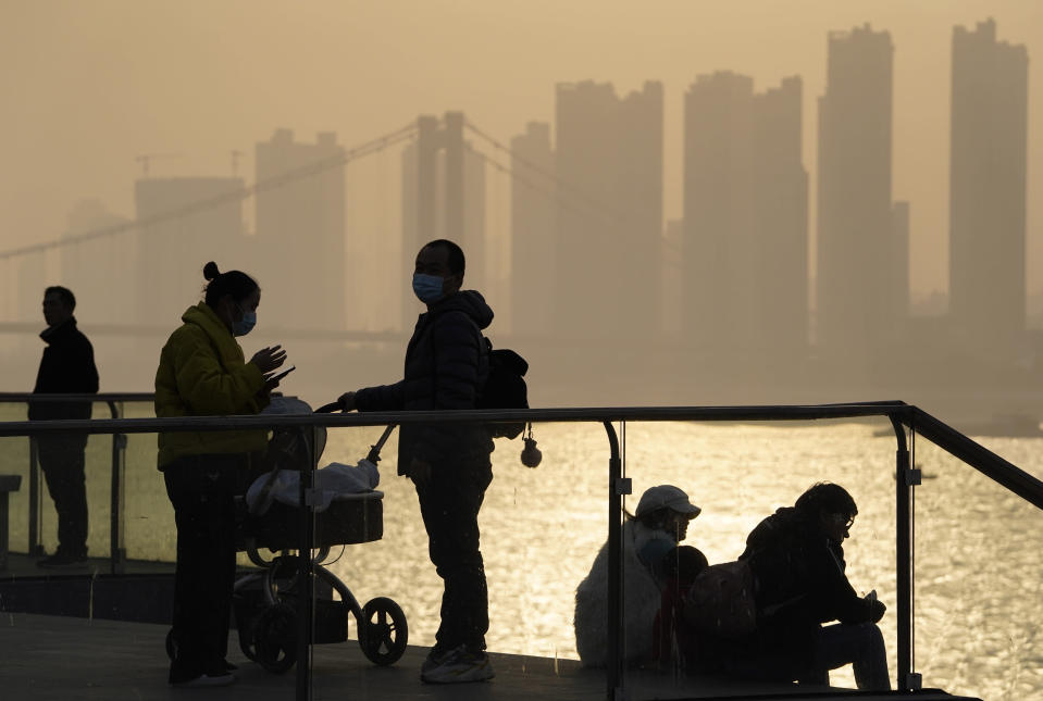 FILE - In this Jan. 15, 2021, file photo, residents enjoy the sunset along the riverbank in Wuhan in central China's Hubei province. Couples go on dates, families dine out at restaurants, shoppers flock to stores. Face masks aside, people are going about their daily life pretty much as before in the Chinese city that was first hit by the COVID-19 pandemic. (AP Photo/Ng Han Guan, File)