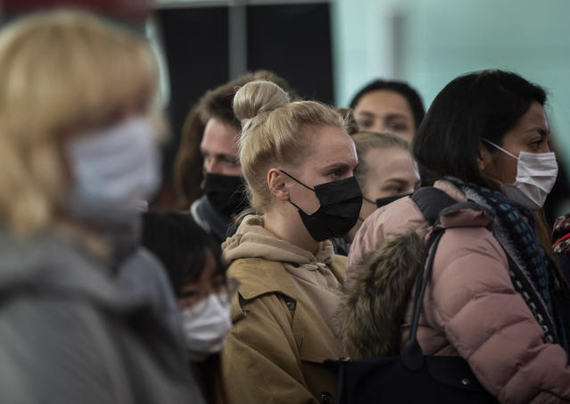 Passengers wearing masks line up as they wait to check in at Barcelona airport, Spain, Saturday, March 14, 2020. Spain's prime minister has announced a two-week state of emergency from Saturday in a bid to contain the new coronavirus outbreak. For most people, the new coronavirus causes only mild or moderate symptoms. For some, it can cause more severe illness, especially in older adults and people with existing health problems. (AP Photo/Emilio Morenatti)
