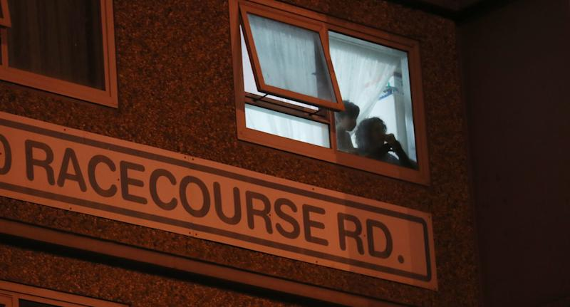 Residents watch out the window of a unit inside a tower on Racecourse Road on Saturday evening. Source: AAP