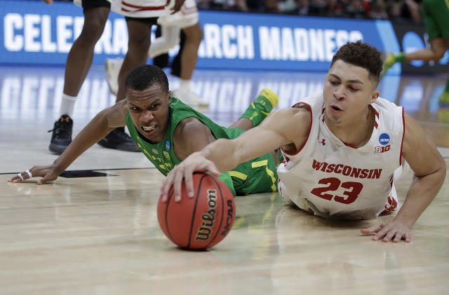 Wisconsin guard Kobe King (23) dives for the ball in front of Oregon forward Louis King during the second half of a first-round game in the NCAA men's college basketball tournament Friday, March 22, 2019, in San Jose, Calif. (AP Photo/Ben Margot)