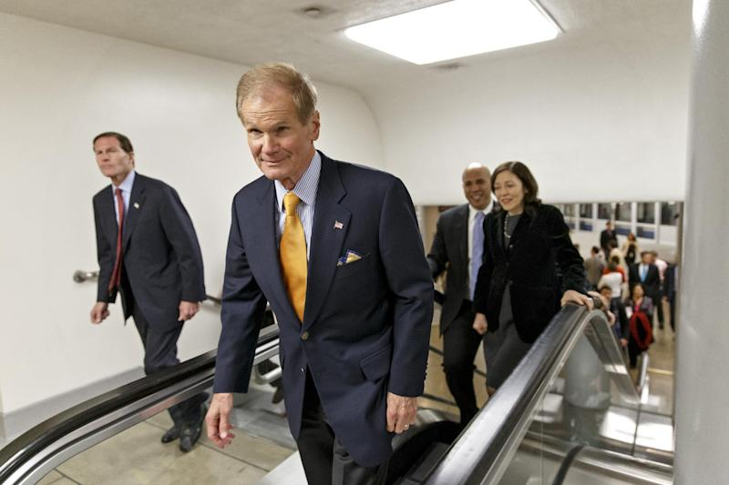 From left to right, Sen. Richard Blumenthal, D-Conn., Sen. Bill Nelson, D-Fla., Sen. Cory Booker, D-N.J., and Sen. Maria Cantwell, D-Wash., rush to the chamber during a procedural vote on a comprehensive defense bill which would provide $552.1 billion for the regular military budget and $80.7 billion for the war in Afghanistan and other overseas operations, at the Capitol in Washington, Thursday, Dec. 19, 2013. The bill also seeks to crack down on sexual assault in the military and add protections for victims. (AP Photo/J. Scott Applewhite)