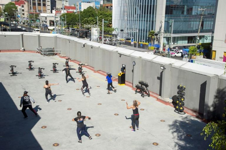 People take a zumba dance class in a parking lot in Mexico City, where a new lockdown is pushing gyms outdoors