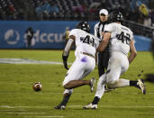 Northwestern safety Jared McGee (41) picks up a fumble next to linebacker Paddy Fisher (42) during the second half of the Holiday Bowl NCAA college football game against Utah Monday, Dec. 31, 2018, in San Diego. McGee returned the fumble for an 86-yard touchdown. (AP Photo/Denis Poroy)