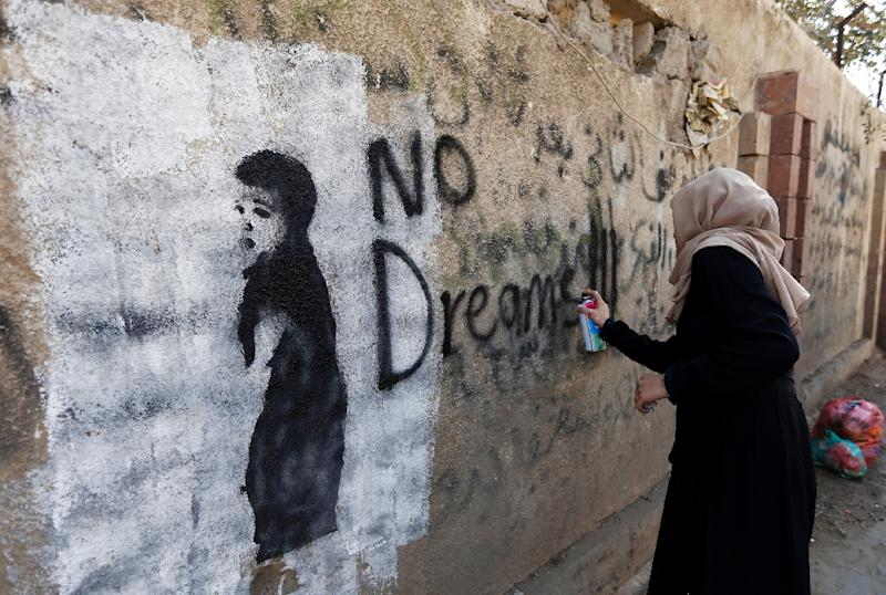A woman paints on a Sanaa wall a day after dozens of women staged a sit-in to demand an end to the country's war. (AFP Photo/Mohammed HUWAIS)