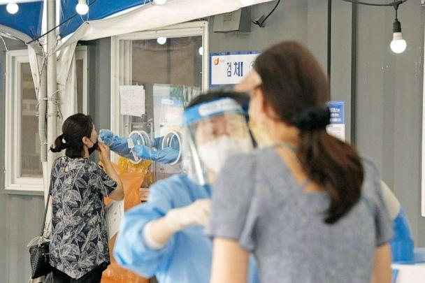 PHOTO: A medical worker in a booth takes a nasal sample from a woman at a Coronavirus testing site in Seoul, South Korea, July 20, 2021.  (Ahn Young-Joon/AP)