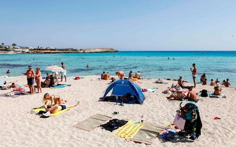 Tourists on a beach on the outskirts of the resort of Ayia Napa in Cyprus - Credit: Amir Makar/AFP