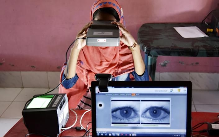 A woman takes an iris scan to link her Aadhar card with National Register of Citizens - DAVID TALUKDAR/AFP