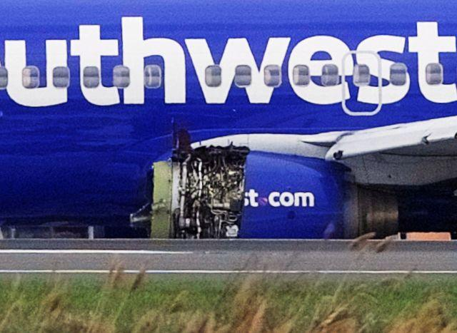 Emergency personnel monitor the damaged engine of Southwest Airlines Flight 1380, which diverted to the Philadelphia International Airport this morning, in Philadelphia, Pennsylvania