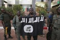 Malian security officials show a jihadist flag they said belonged to attackers in front of the Radisson hotel in Bamako, Mali, November 20, 2015. REUTERS/Joe Penney