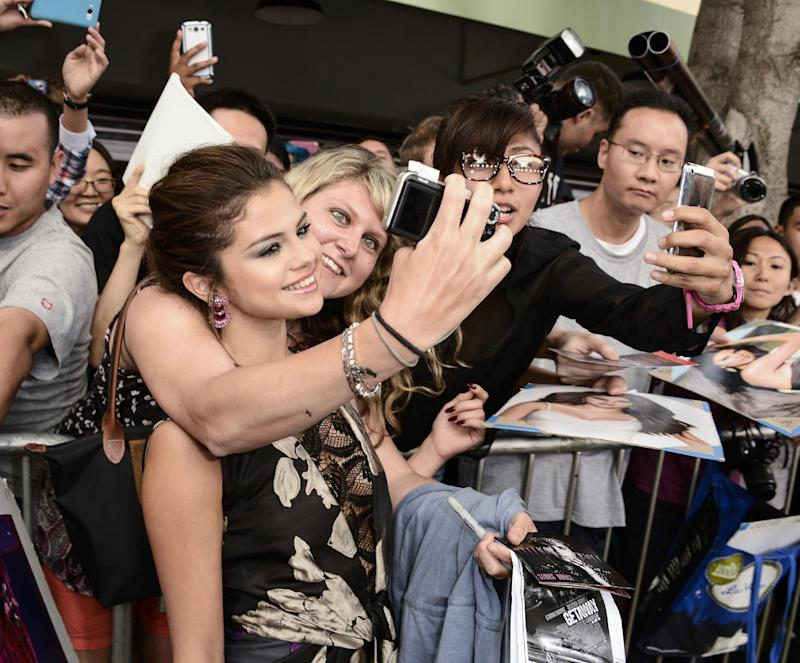 "Actress Selena Gomez poses for a photo with a fan on the red carpet at the premiere of the feature film ""Getaway"" at the Regency Village Theater on Monday, Aug. 26, 2013 in Los Angeles. (Photo by Dan Steinberg/Invision/AP)"