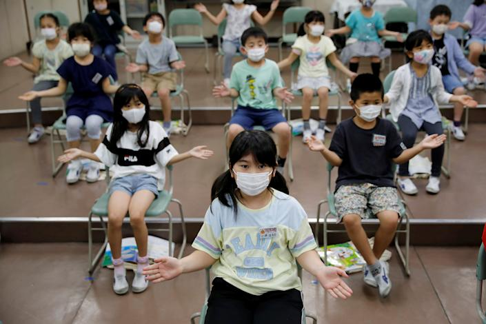 Students wearing protective face masks amid the coronavirus pandemic clap along instead of singing in a music class at Takanedai Daisan elementary school, which practices various methods of social distancing in order to prevent the infection, in Funabashi, east of Tokyo.