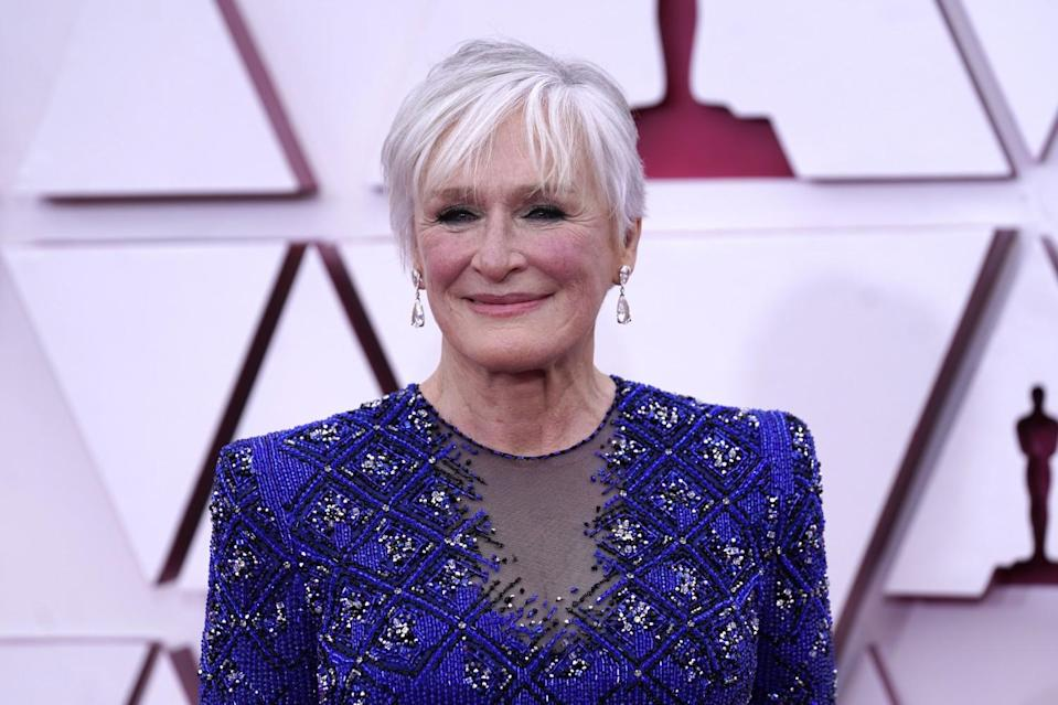 Wearing a blue patterned tunic with silk pants and evening gloves, Glenn Close arrives at the Oscars.