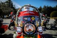 A man dressed in Santa Claus costume wearing protective face mask rides his motorbike before Xmas Toy Run parade amid the coronavirus disease (COVID-19) outbreak, in Tokyo