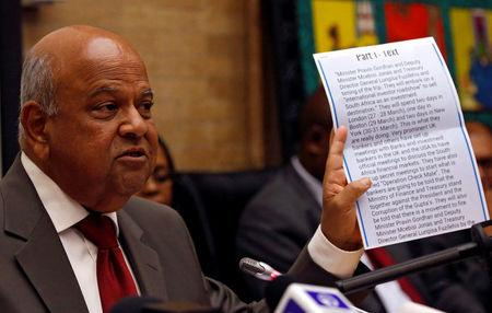 South Africa's outgoing Finance Minister Pravin Gordhan holds a copy of an intelligence report that President Jacob Zuma used as justification to fire him, during a media briefing at their offices in Pretoria, South Africa