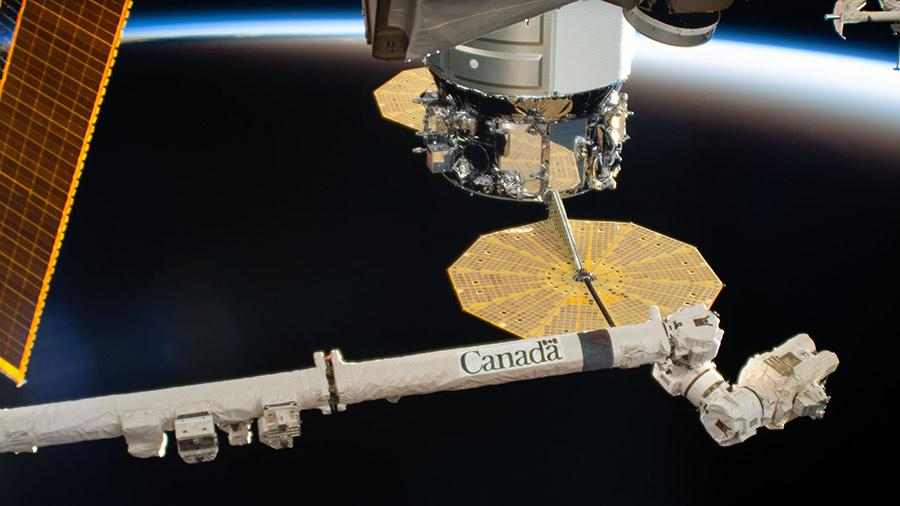 This photo shows the Canadarm2 robotic arm at the International Space Station which continues to orbit around Earth from 254 miles (409 kilometers) away. The robotic arm, a collaboration with Canada, helps to make repairs on the space station and astronauts have used it complete activities on spacewalks outside of the space station.