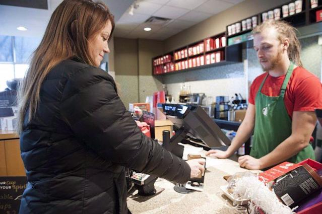 Maureen Turner uses her phone to pay for her coffee at a Starbucks in Mississauga, Ont. on Saturday, Dec. 19, 2015. (THE CANADIAN PRESS/Hannah Yoon)