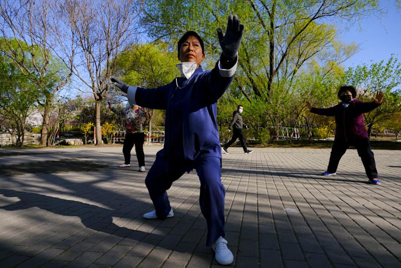 A woman in Beijing with a face mask performs Tai Chi part of precautionary measures against the spread of the COVID-19 on April 02, 2020 in Beijing, China.