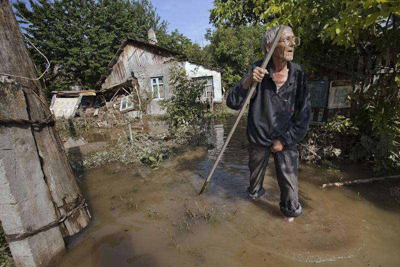 A local resident stands at a flooded house in Krimsk, about 1,200 kilometers (750 miles) south of Moscow, Russia, Sunday, July 8, 2012. The death toll from severe flooding in the Black Sea region of southern Russia has risen to at least 150. (AP Photo/Ignat Kozlov)