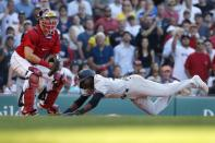 New York Yankees' Estevan Florial, right, scores on an RBI-single by Brett Gardner as Boston Red Sox's Kevin Plawecki, left, waits for the throw during the eighth inning of a baseball game, Saturday, July 24, 2021, in Boston. (AP Photo/Michael Dwyer)