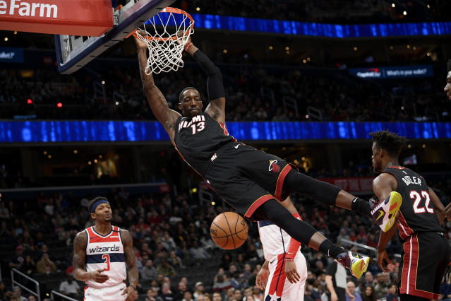 Miami Heat forward Bam Adebayo (13) swings from the rim after his dunk during the first half of an NBA basketball game as Washington Wizards guard Bradley Beal (3) looks on Sunday, March 8, 2020, in Washington. (AP Photo/Nick Wass)