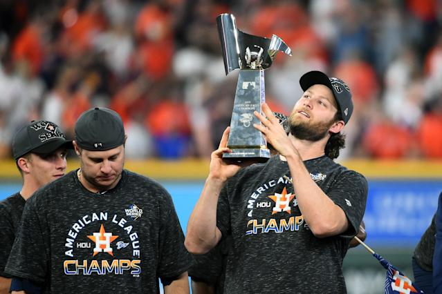 Gerrit Cole (right) celebrates with the ALCS trophy Saturday night. (Photo by Cooper Neill/MLB Photos via Getty Images)