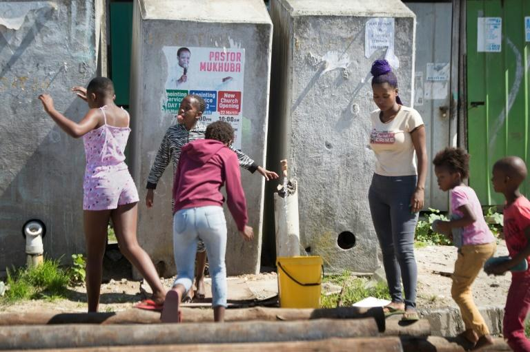 A woman fills a bucket from a communal tap as children play (AFP Photo/RODGER BOSCH)
