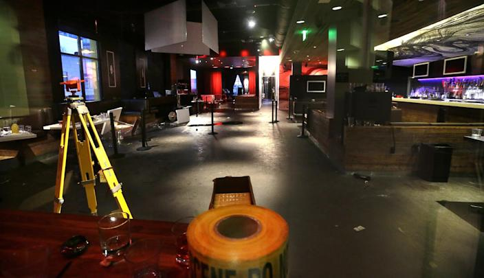 The interior of the Munchbar, where tables are seen overturned and debris strewn about, is photographed Monday, Dec. 24, 2012, in Bellevue, Wash.. A 30-year-old Seattle man was killed and another man wounded in a shooting at the crowded bar earlier in the morning about 10 miles east of Seattle. (AP Photo/Elaine Thompson)