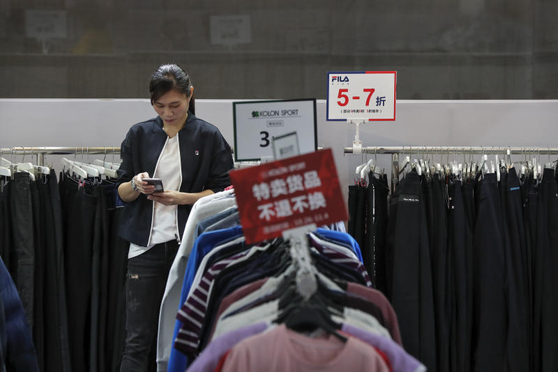 FILE - In this Nov. 1, 2019, file photo, an employee browses her smartphone at a clothing store having a promotion sale at a shopping mall in Shenzhen, China's Guangdong province. China has raised its estimate of the size of its economy by 2.1% following a census, raising its gross domestic product for 2018 to 91.93 trillion yuan ($13.1 trillion), the National Bureau of Statistics said Frida, Nov. 22, 2019. (AP Photo/Andy Wong, File)
