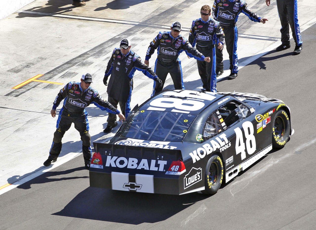 Crew members high-five Jimmie Johnson as he leaves pit road prior to the start of the NASCAR Sprint Cup Series auto race, Sunday, March 4, 2012, at Phoenix International Raceway in Avondale, Ariz. (AP Photo/Matt York)