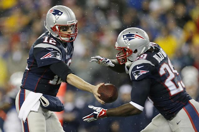 New England Patriots quarterback Tom Brady (12) hands off the ball to running back LeGarrette Blount (29) during the first half of an AFC divisional NFL playoff football game against the Indianapolis Colts in Foxborough, Mass., Saturday, Jan. 11, 2014. (AP Photo/Michael Dwyer)