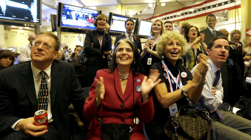 Angelique Fernandez of New York, second from right, with her friend Sidney Ross, second from left, both supporting President Barack Obama react to early election results during the Presidential Election party at the U.S. Embassy in London, Wednesday, Nov. 7, 2012. (AP Photo/Alastair Grant)