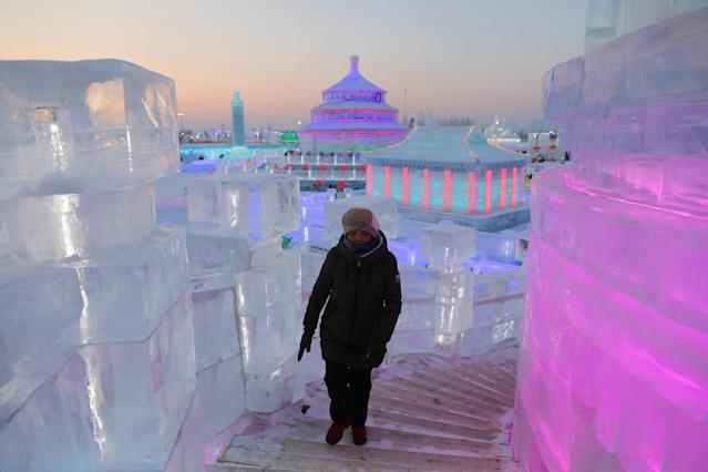 <p>A woman visits the ice sculptures illuminated by colored lights at the 34th Harbin International Ice and Snow Festival on Jan. 4. (Photo: Wu Hong/EPA-EFE/REX/Shutterstock) </p>