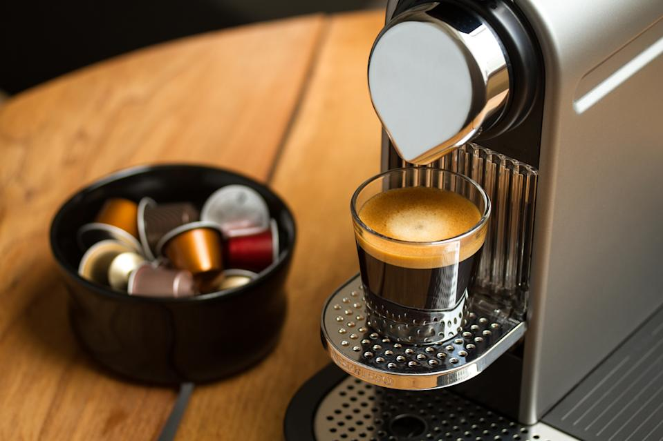 Freshly brewed espresso in glass standing on silver Nespresso coffee machine. Blurred background with Nespresso capsules in black bowl.
