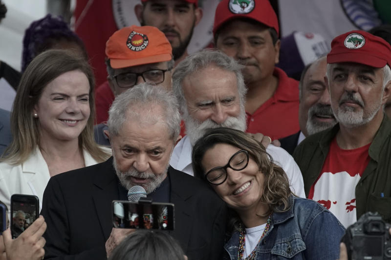 Brazil's former President Luiz Inacio Lula da Silva speaks to supporters as his girlfriend Rosangela da Silva leans on his shoulder after he was released from jail where he was imprisoned on corruption charges in Curitiba, Brazil, Friday, Nov. 8, 2019. Da Silva walked out of the Curitiba prison Friday, less than a day after the Supreme Court ruled that a person can be imprisoned only after all the appeals have been exhausted. (AP Photo/Leo Correa)