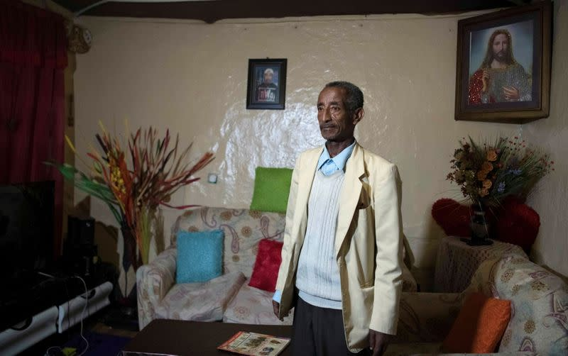 Ayalew Wedajo poses for a photograph inside his house during an interview with Reuters in Addis Ababa