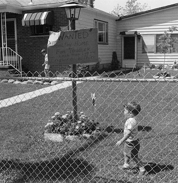 FILE - In this Aug. 4, 1978 file photo, children play in the front yard of their home on 99th Street in the Love Canal neighborhood of Niagara Falls, N.Y. The children's parents were among irate homeowners whose property was built over a former dumping site for toxic chemicals. (AP Photo/TK)