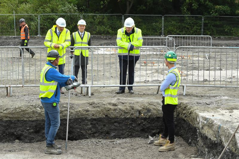 Britain's Prime Minister Boris Johnson speaks with workers as he visits the Speller Metcalfe's building site in Dudley