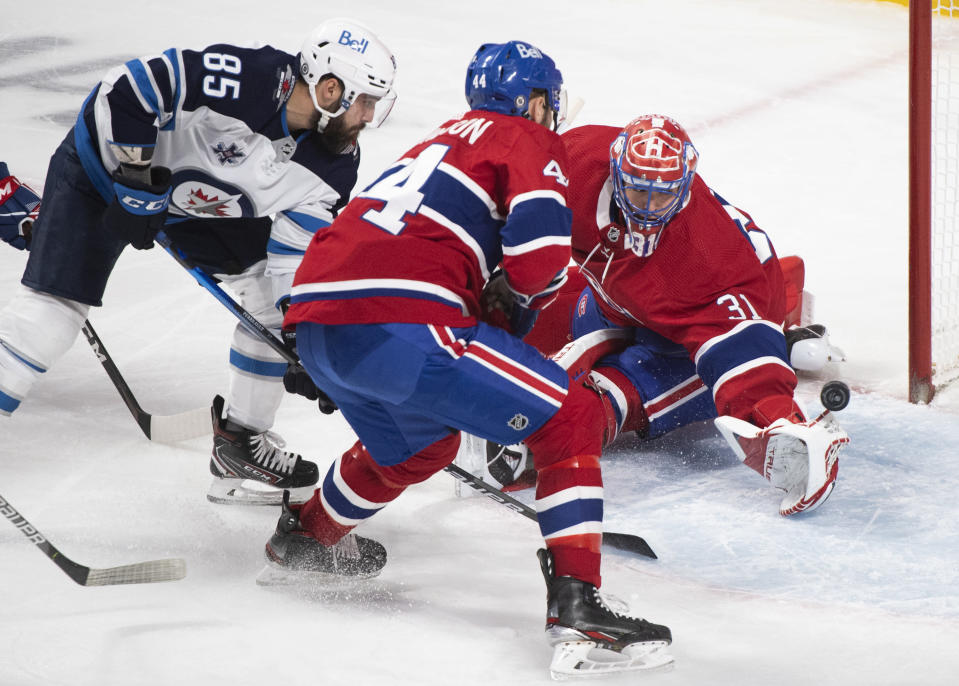 Winnipeg Jets' Mathieu Perreault (85) scores against Montreal Canadiens goaltender Carey Price as Canadiens' Joel Edmundson defends during the third period of an NHL hockey game Saturday, March 6, 2021, in Montreal. (Graham Hughes/The Canadian Press vIa AP)