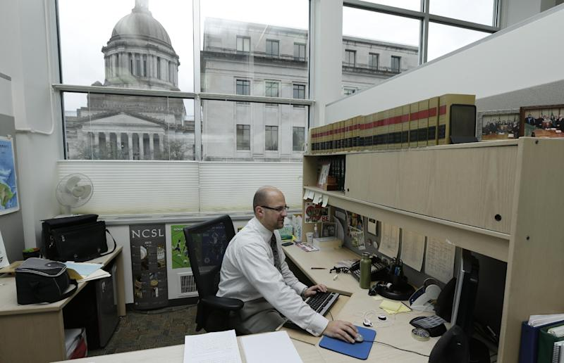 Brandon Popovac, an assistant code reviser at the Capitol in Olympia, Wash. works next to a printed stack of paper awaiting gender-neutral corrections, Wednesday, Jan. 30, 2013. Washington state legislators are nearing the completion of a multiyear project to replace thousands of references to male-centric words in state law with gender-neutral terms. (AP Photo/Ted S. Warren)