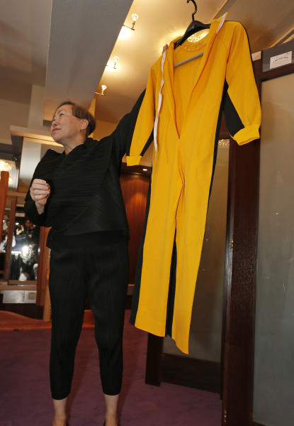 "Anna Lee, vice-chairman of Spink auction house, holds Bruce Lee's original yellow jumpsuit he wore in ""Game of Death"" during an auction preview in Hong Kong, Monday, Dec. 2, 2013. It's part of a collection of 14 items including clothing and props going on the block on Thursday. Lee died in 1973, before the movie was finished. Spink estimates the suit will fetch 250,000 to 300,000 Hong Kong dollars ($32,250-$38,700). (AP Photo/Vincent Yu)"
